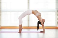 Young woman practices yoga at gym by window stock photos