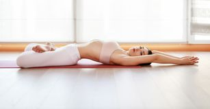 Young woman practices yoga at gym by window stock photo