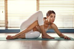 Young woman practices yoga at gym by window royalty free stock image