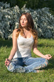 Young woman practices yoga and meditates Royalty Free Stock Photo