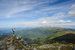 Young woman practices yoga on a mountain top Stock Photos