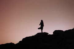 Young woman practices yoga at sunrise Royalty Free Stock Images