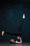 Young woman practicing advanced yoga on blue mat Royalty Free Stock Photography