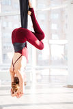 Young woman practicing antigravity yoga exercises in studio Royalty Free Stock Photography