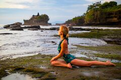 Free Young Woman Practicing Ardha Kapotasana, Half Pigeon Pose. Chest Opener Improving Breathing. Water Reflection. Tanah Lot Beach, Stock Photo - 176977500