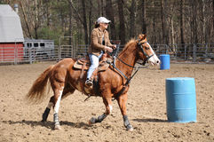 Young woman practicing barrel racing. A young woman turns around a barrel and heads to the finish line Royalty Free Stock Photography