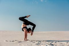 Young woman practicing handstand on beach with white sand and bright blue sky. Young woman practicing inversion balancing yoga pose handstand on beach with white Royalty Free Stock Photography