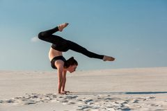 Young woman practicing handstand on beach with white sand and bright blue sky. Young woman practicing inversion balancing yoga pose handstand on beach with white Stock Image