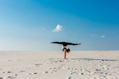 Young woman practicing handstand on beach with white sand and bright blue sky Stock Photo