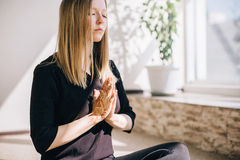 Young woman practicing meditation indoors. Holds hands together in prayer Stock Images