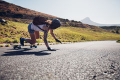 Young woman practicing skateboarding on rural roads Stock Images
