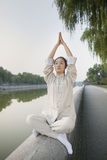 Young Woman Practicing Tai Ji, Arms Raised, by the Canal Stock Image
