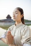 Young Woman Practicing Tai Ji, Hands together and eyes closed, Outdoors stock photo