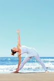 Young woman practicing yoga. On the beach Stock Photo
