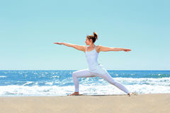 Young woman practicing yoga. On the beach Royalty Free Stock Photo