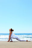 Young woman practicing yoga. On the beach Royalty Free Stock Photos