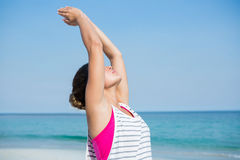Young woman practicing yoga with arms raised at beach. Against clear blue sky Royalty Free Stock Photos