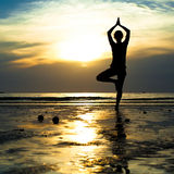 Young woman practicing yoga on the beach Royalty Free Stock Images