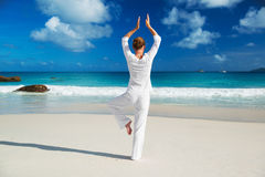 Young woman practicing yoga on the beach Stock Photos