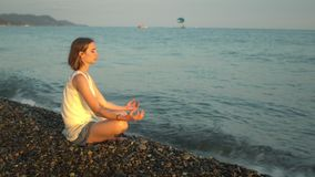 Young woman practicing yoga on the beach and suddenly splashes a wave. Sunset