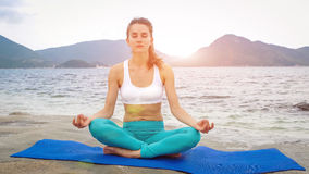 Young woman practicing yoga on the beach at sunset. Lotus pose Royalty Free Stock Images