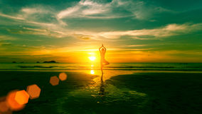 Young woman practicing yoga on the beach Stock Photography