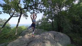 Young woman is practicing yoga at beautiful exotic place on the top of a mountain in slow motion. Yoga and meditation stock video footage