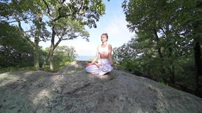 Young woman is practicing yoga at beautiful exotic place on the top of a mountain in slow motion. Yoga and meditation stock footage