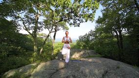 Young woman is practicing yoga at beautiful exotic place on the top of a mountain in slow motion. Yoga and meditation stock video