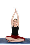 Young woman practicing yoga on a blue mat Stock Photography