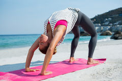 Young woman practicing yoga in bridge position at beach Stock Photography