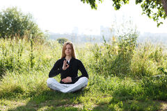 Young woman practicing yoga in the city park Royalty Free Stock Photography
