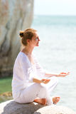 Young woman practicing yoga by coast Stock Photos