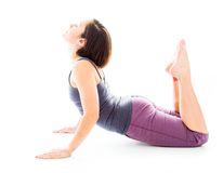 Young woman practicing yoga in cobra pose. Young adult caucasian woman isolated on a white background Stock Images