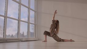 Young woman practicing yoga and doing lunge stock footage