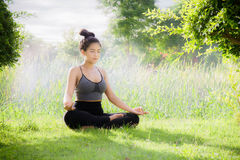 Young woman practicing yoga Everyday Yoga helps in concentration. Breath, shape body, strength, help skin brighten. Among the Dharma Air in bright days stock photography