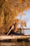 Young woman practicing yoga exercise at quiet pier in autumn park.  stock image