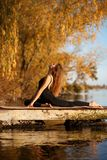 Young woman practicing yoga exercise at quiet pier in autumn park.  stock photos