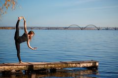 Young woman practicing yoga exercise at quiet wooden pier with c. Ity background. Sport and recreation in city rush royalty free stock photography