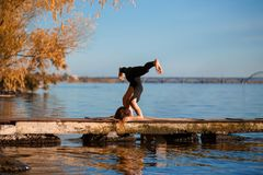 Young woman practicing yoga exercise at quiet wooden pier with c. Ity background. Sport and recreation in city rush stock photos