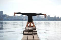 Young woman practicing yoga exercise at quiet wooden pier with city background. Sport and recreation in city rush.  royalty free stock photography