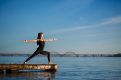 Young woman practicing yoga exercise at quiet wooden pier with city background. Sport and recreation in city rush.  royalty free stock photos