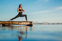 Young woman practicing yoga exercise at quiet wooden pier with city background. Sport and recreation in city rush.  stock images