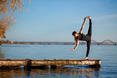 Young woman practicing yoga exercise at quiet wooden pier with city background. Sport and recreation in city rush.  royalty free stock photo