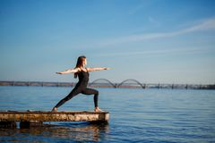 Young woman practicing yoga exercise at quiet wooden pier with city background. Sport and recreation in city rush.  royalty free stock image
