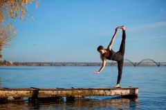 Young woman practicing yoga exercise at quiet wooden pier with city background. Sport and recreation in city rush.  stock image