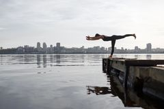 Young woman practicing yoga exercise at quiet wooden pier with city background. Sport and recreation in city rush.  royalty free stock images