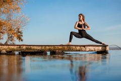 Young woman practicing yoga exercise at quiet wooden pier with city background. Sport and recreation in city rush.  stock photos