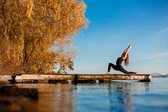 Young woman practicing yoga exercise at quiet wooden pier with city background. Sport and recreation in city rush.  stock photo