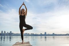 Young woman practicing yoga exercise at quiet wooden pier with city background. Sport and recreation in city rush.  stock photography